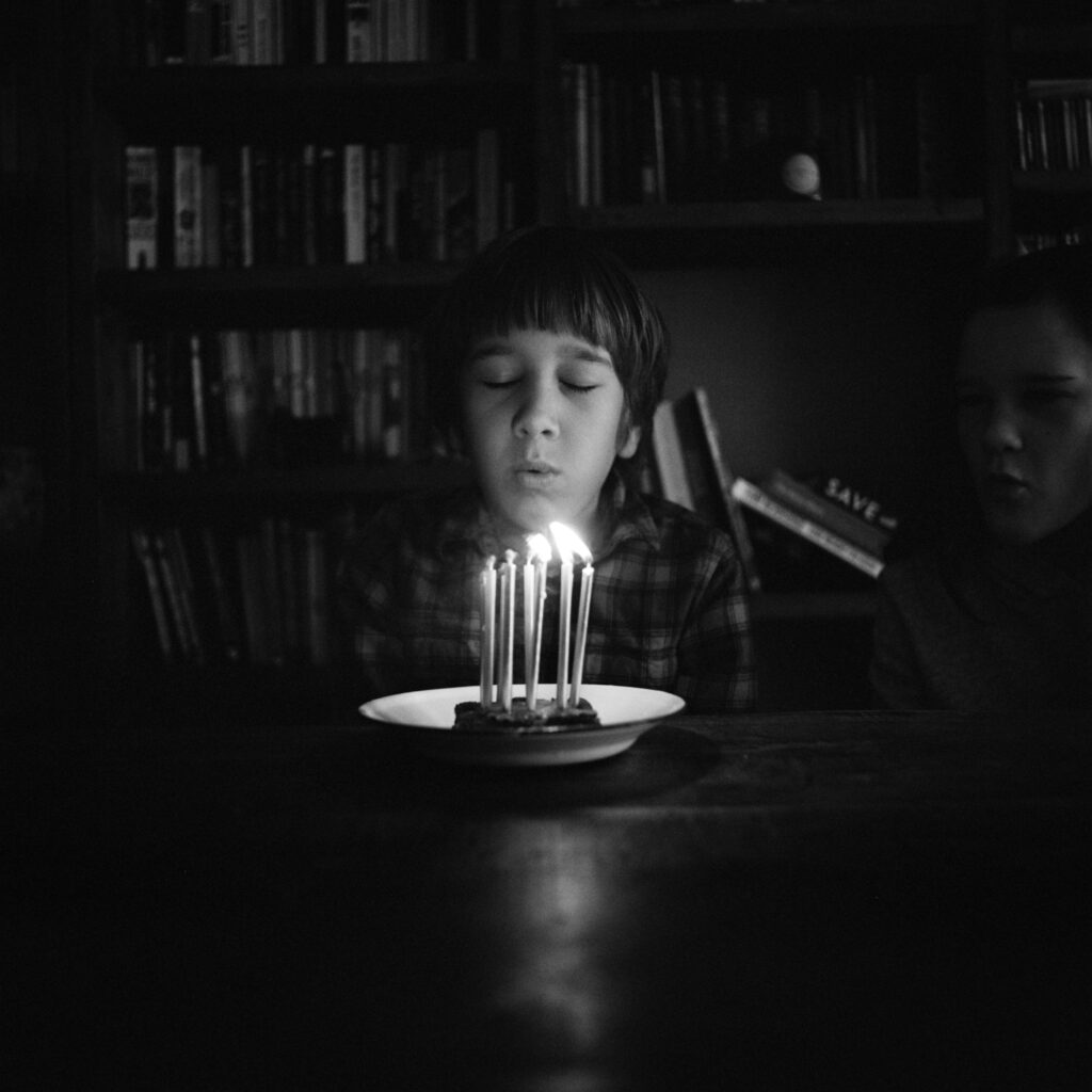 Black and white picture fo a boy about to blow out the candles on his birthday cake. Photo is in an advertising article for Wicked Uncle. Photo by Annie Spratt on Unsplash.