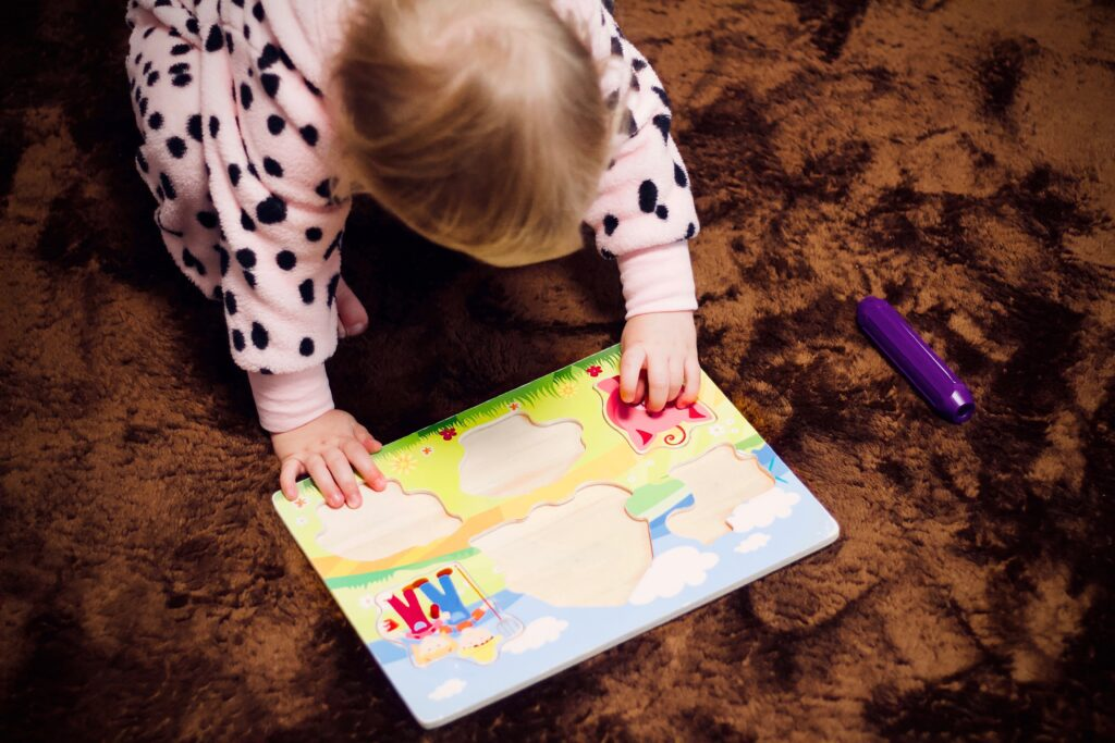 Picture taken from overhead of a small child playing with a wooden puzzle on the floor.