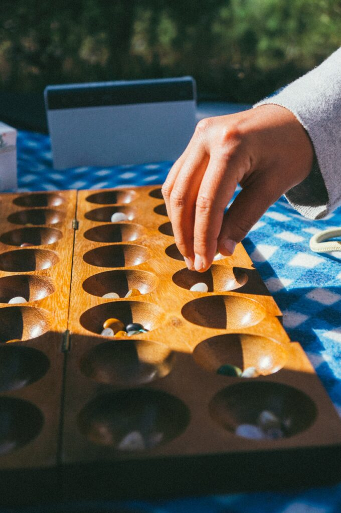 Photo of someone playing a game similar to Mancala with stones and a wooden tray.