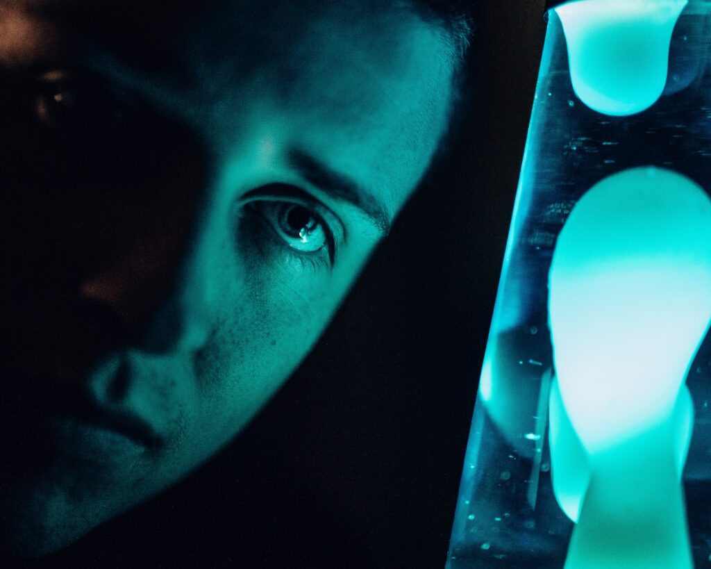 A close up photograph showing a male teen face staring at a mood light. Illustrating an article entitled: Gift ideas to get boys away from screens this Christmas